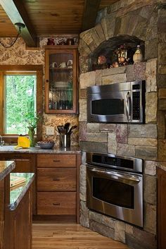This rustic kitchen corner has stacked eye level ovens enclosed in natural stone.