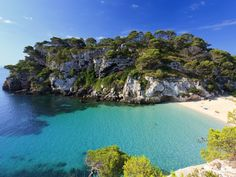 Located on the sun-bleached southwestern coast of Menorca, the tranquil Cala Macarella is the ideal escape from the congested beaches of nearby Mallorca and Ibiza. Getting there is a trek: you can either hike two miles along the cliffs from nearby Cala Galdana, or drive on a rough and winding road from Ciutadella and hike an additional 20 minutes through a pine forest to get there (phew). But its ultra-fine sand and calm turquoise waters are well worth the effort.