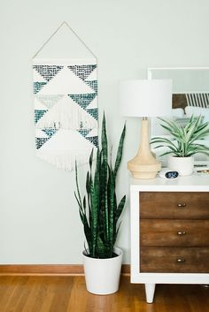 Living space with a knitted wall hanging and a snake plant