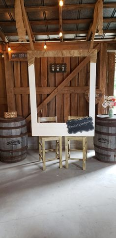 Photo props in mason jar on top of whiskey barrel with hanging frame