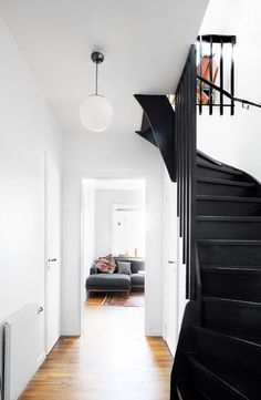 black staircase and white walls with globe pendant light fixture. Decor, House Design, Interior Design, House Interior, Home, House, White Walls, Black Staircase, Stairs