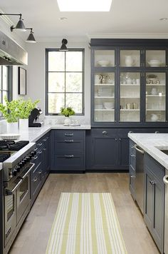 Black (or dark grey) cabinets in this kitchen with white marble countertops.  I like how the interior of the built-in china hutch is also painted white and filled with white china.  Accents of green.