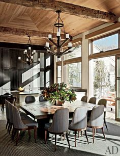 A rustic dining room featuring brushed oak cabinetry and vintage French chandeliers | archdigest.com