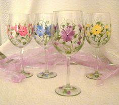 Un arc-en-ciel de fleurs sauvages main peinte sur un ensemble de quatre verres de vin