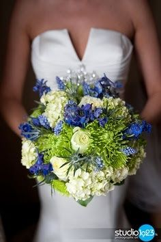 Replace most of the green with orange/red proteas.  Bouquet wrapped with teal satin ribbon.