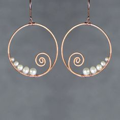 The scroll hoop earrings are handmade using copper wire and fresh water pearl.Free US shipping. The dimension of the hoop is 1 3/4inches, 45mm. A spiral is creative and free. As it appears in nature , the scroll is associated with growth, life, energy and transformation. This design