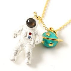 This fun space themed **necklace** from **gargle** has a cute **astronaut pendent** attached to a **gold chain** plus a shiny **green planet** too. The astronaut's helmet also has a lovely, shiny finish on his visor so he's all ready to enjoy some space themed fun in your everyday adventures.