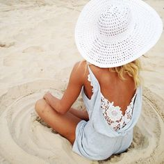 tan girl in floppy white hat and light blue romper at the beach http://www.itgirlweddings.com/blog/8-items-to-pack-for-your-beach-honeymoon