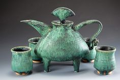 """Teapot thrown and altered with slab spout, feet carved from extrusions. Glaze a green crystalline mat. Teapot 9"""" x 5"""" x 8"""""""