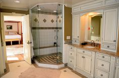 Walk-in shower with glass doors and seat in master bathroom