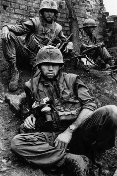 Two grizzled Marine infantrymen and a battle-weary combat cameraman pause for a brief respite from the savage urban fighting that defined the battle for Hue City.