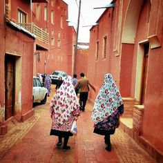 Women in traditional dresses walking in #Abyaneh (W/ red soil and houses) locatd 70km SE of #Kashan #Iran by @Moqimi