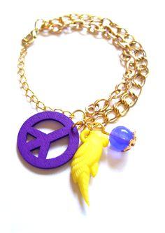 Pulsera dorada doble con papagayo de color amarillo y símbolo paz violeta
