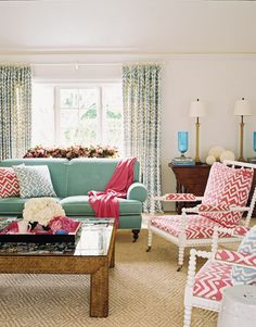 Green rolled arm sofa with caster legs, pink throw, pink and blue geometric pillows, white chairs with pink cushions, jute rug, drapes and coffee table.