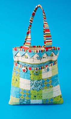 This simple open-top patchwork bag cleverly incorporates a deep outer pocket and fabric-covered buttons.