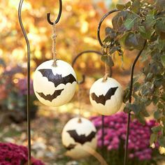 Hanging Bat Pumpkins. Skip the carving and cast a spell by drawing bats on white pumpkins using a permanent marker. To hang, cut a length of thick jute and knot one end through a large washer. Drill a hole in the top and bottom of each pumpkin and use wire to pull the twine through the holes. The washer supports the pumpkin's weight; the jute loop attaches to a shepherd's hook. (#BHG)