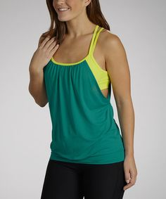 The perfect blend of loose and fitted, this colorful tank is an ideal workout partner. Flattering gathers and a deep side cutout make for cooler activities. Tank: 90% polyester / 10% spandexBuilt-in-bra: 100% polyester mesh