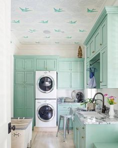 This minty laundry room (spotted on Houzz via FLOY) with its Daydream (Green) fifth wall proves that the best place to use wallpaper is everywhere!