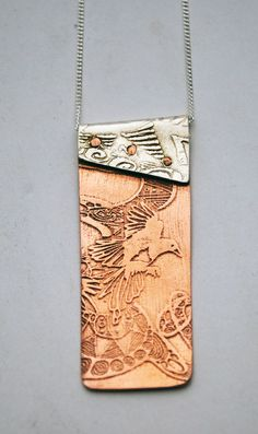 This copper and silver Magpie necklace is made up of two etched and impressed pieces of metal and riveted together with handmade copper rivets. The