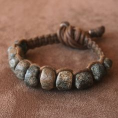 by Ryan Keane | Bracelet; 1000 Year Old or more Granite Stone Beads from Mali are on Hand Woven Brown Waxed Linen with solid Lost Wax Bronze Grips (Sealed) | 60$