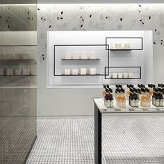 Black frames outline rows of olive oil bottles at this culinary shop in Toronto, while images of olive branches decorate the walls behind.