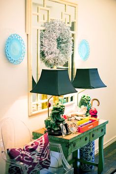 Colorful foyer vignette with foo lamps, ghost chair, ikat pillow, chinoiserie mirror, blue and white umbrella stand, green painted piece--love the style and sense of fun.