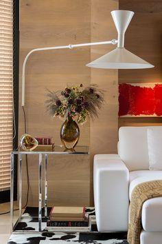 Sala de estar com sofá branco, luminária, quadros, parede revestida com madeira, mesa lateral e tapete de vaca.