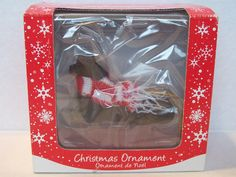 One Sandicast Dog Ornament for Hanging on the Christmas Tree.  Dachshund, Black Color, Item XSO04405, UPC 746314015599 and wearing a Scarf  Packaging states that the Dog Ornament has been Hand Cast and Hand Painted.
