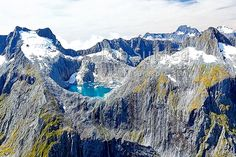Glacial meltwater lake between Llawrenny Peaks and Terror Peak with icebergs. With Mounts Grave and Tutuko peaks behind, Fiordland National Park, Southland District, Southland Region, New Zealand (NZ).