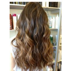 Ombre on virgin hair using high lift hair color . Light brown and dark brown balayage highlights. Curls using a wand . Long layered hair cut