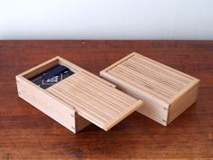 Two boxes, made of white oak. Joined at the corners with dovetails. Two compartments, separated by a small divider. Silk lifting ribbon set with brass tacks. Accented grooves cut into the sliding box lid. Finished lightly with shellac.