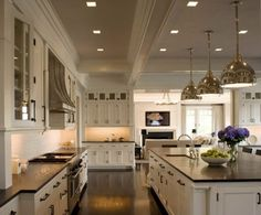 Amazing floor plan for dream kitchen - Creamy white kitchen cabinets & kitchen island with black granite countertops, sink in kitchen island and industrial pendants.