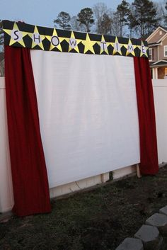 """Movie screen was made with a roll of white coated paper,attached to 4 long 2x4's on the top and bottom, and one on each side to make a frame...2 red twin sheets, and staple gunned them to the top to look like curtains. the banner across the top was made with black scrapbook paper and 12"""" gold stars found at Oriental Trading."""