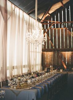 Barn style wedding with soft drapes and one gorgeous chandelier! Photo: Style Me Pretty