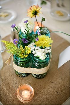 group mason jars for an easy table arrangement and place an ecclectic array of flowers....no florist needed for this!
