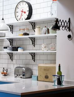 Sustainable Kitchens - Industrial Kitchen with American Diner Feel. White shelving on vintage Duckett design brackets attached to white metro tiles with dark grout work well with the bianco venato worktop for the breakfast bar.