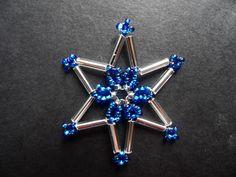 Modrostříbrná vánoční hvězda Hvězdička má průměr 4,5 cm a je vyrobena z rokajlových korálků a tyček. Střed hvězdičky tvoří tmavě modrá kytička. Hvězdičky se hodí jako vánoční ozdoba na stromeček, nebo na ozdobení adventního věnce nebo dárku.