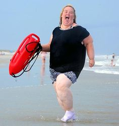 """June """"Mama Bear"""" Shannon runs on the beach with a lifeguard buoy in Tybee Island, Georgia on June 12, 2013."""