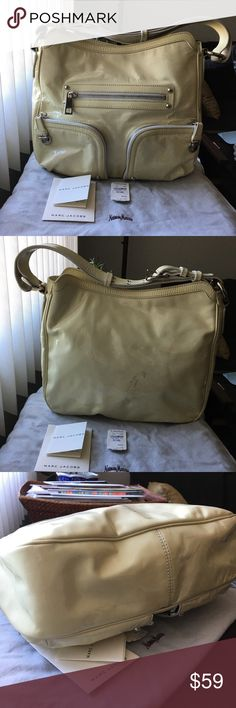 """MARC JACOBS Yellow Patent Leather Christy Hobo Authentic Marc Jacobs Christy hobo in pale yellow patent leather with silver hardware. Comes with Neiman Marcus dustbag, care paperwork and tags. MSRP $1175, purchased from Neiman Marcus. In fair condition, color transfer, wrinkling and marks throughout; minor wear on corners and handles; hardware in good condition and in working order; removable shoulder strap in good condition. Leather in good condition. Very clean inside. Measurements: 13""""L x…"""