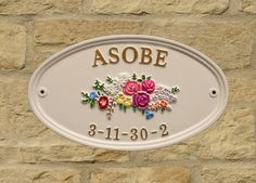 White sign with garland motif with gold letters. sent to Japan. www.rockartisansigns.co.uk