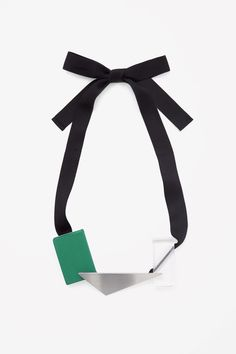 This fabric-tie necklace has large block-shaped beads and a flat metal triangle pendant for a modern collage effect.