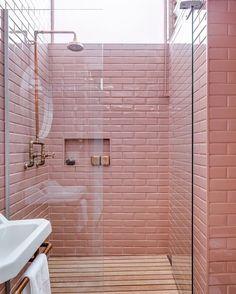 """Banheiro fofo com """"azulejo de metrô"""" rosa e tubulação hidráulica aparente."""