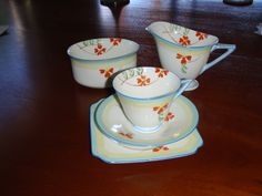 Doulton deco: unnamed tea set incl tea trios, milk jug / creamer and sugar bowl, V1309, c1932 (pattern). Stylised branched orange flowers with yellow and blue border and blue highlights and trim.
