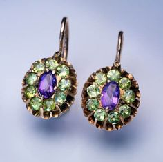 Antique Russian 14k rose gold earrings, each centered with an oval amethyst surrounded by sparkling golden-green demantoids, Moscow, 1899-1908.