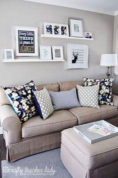 Mensole per quadri alle spalle di un divano dallo stile classico.Fantasie floreali e geometriche per i cuscini danno brio agli accostamenti