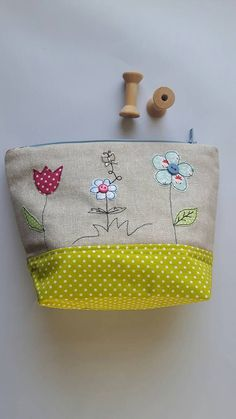 Flower applique zipped pouch/cosmetic case/toiletry bag/wash bag/pencil case is ideal as a storage bag for girls as well as a make-up bag/toiletry case for flower lovers with beautiful colours which immiediatelly makes you think of spring or sunshine! On the front there are 3 flowers with tiny butterfly appliqué on a plain oatmeal cotton/ linen fabric, with a coordinating bottom fabric and lining. Due to its flat bottom and the use of interfacing between the layers of fabric, it will stand…