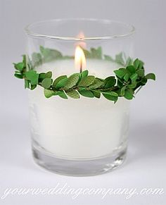 Classic white votive candle with a boxwood garland accent. http://www.yourweddingcompany.com