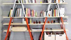 Uma estante decorativa e fácil de montar com  escadas e táboas de madeira.