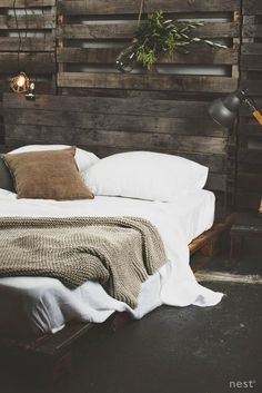 Rustic bedroom with      Rustic bedroom with a dark pallet bed and pallet covered walls. Black floor and white bedding with a beige bedspread.