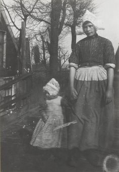 Vrouw en meisje in Volendammer dracht. De vrouw is gekleed in werkdracht. Ze draagt een gedessineerd jak. Het meisje draagt een 'kleedje' (jurkje), met daarover een lijfbontje (schortje). Molkenboer 1915 #NoordHolland #Volendam